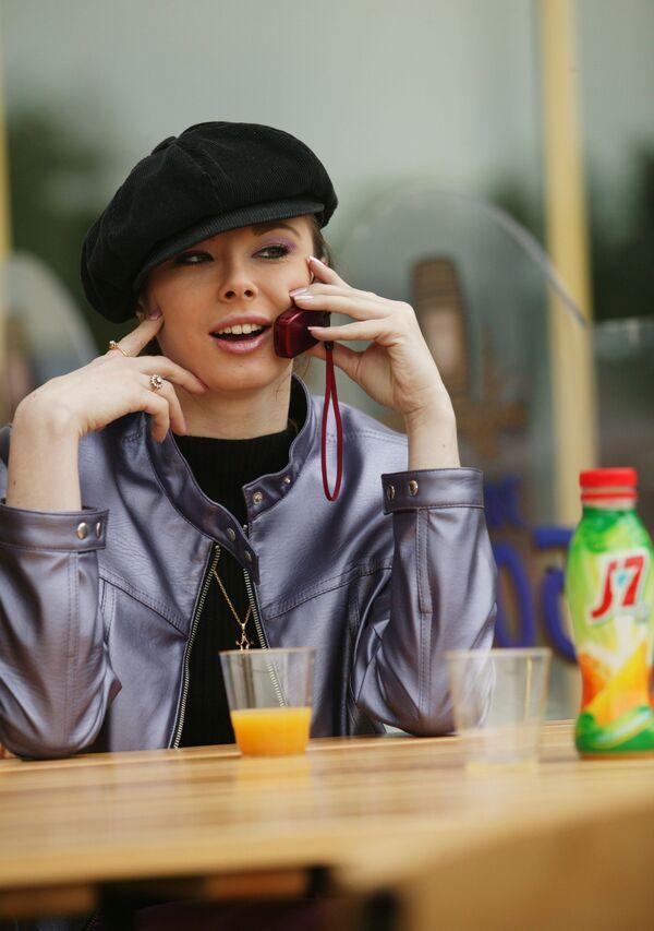 Mosca, 2004 - una ragazza parla al cellulare del suo succo di frutta preferito - Sputnik Italia