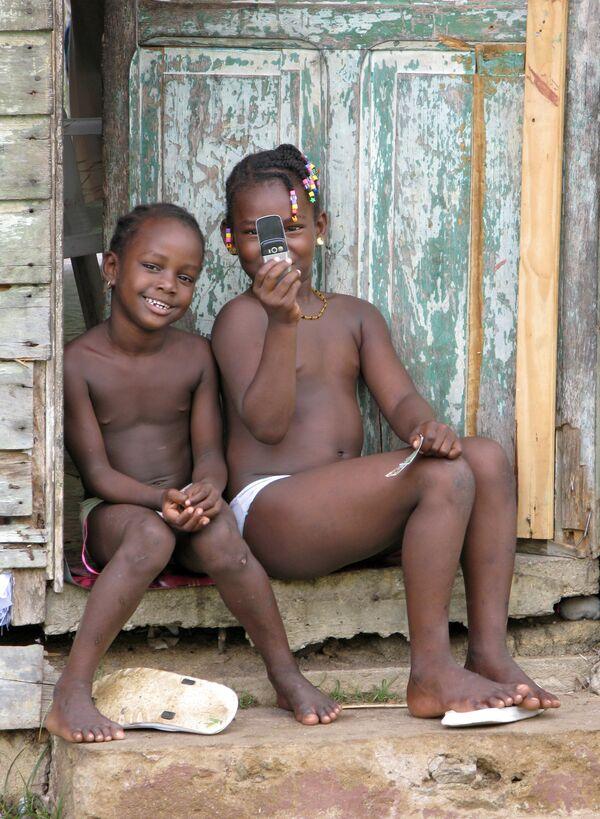 Guyana Francese, 2007 - due bambini del villaggio di Sinnamary fotografano il fotografo russo Alexey Panov con il proprio telefonino  - Sputnik Italia