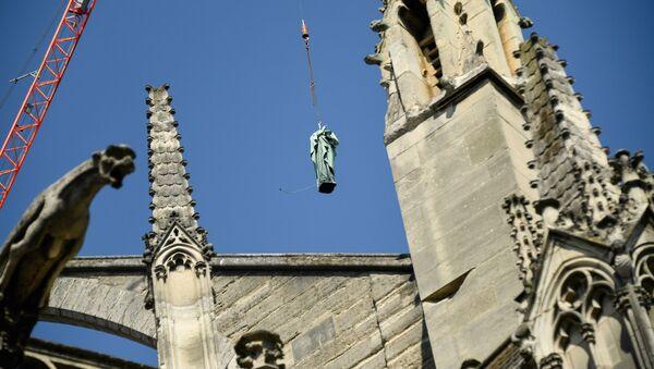 Una statua in rame viene rimossa per essere restaurata dopo l'incendio nell Cattedrale di Notre Dame a Parigi - Sputnik Italia