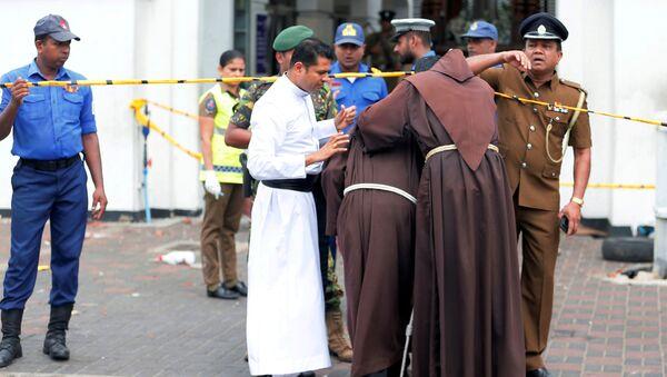 Un prete sta vicino a una chiesa dopo le esplosioni in Sri Lanka - Sputnik Italia