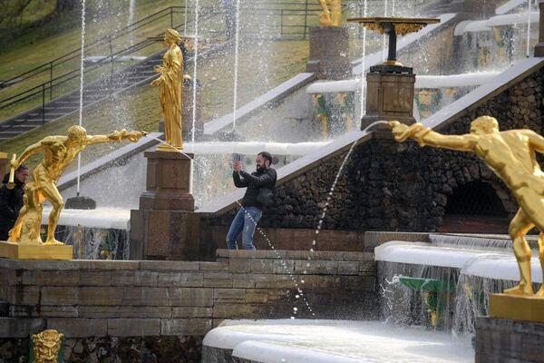 A San Pietroburgo il tempo è spesso variabile, ma nei rari giorni di sole e caldo estivo, i turisti apprezzano particolarmente gli schizzi delle fontane dorate di Petergof - Sputnik Italia