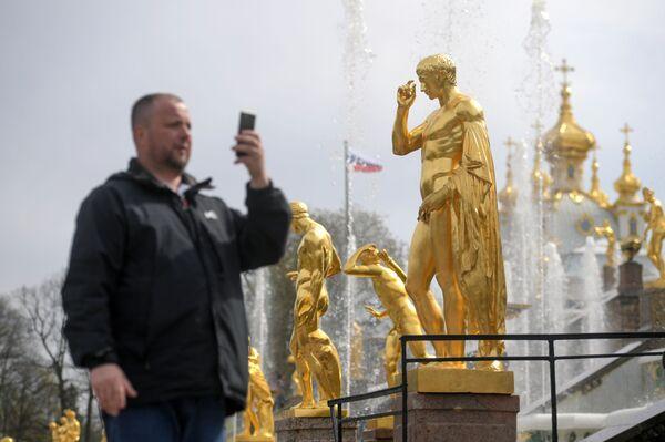 Un turista fotografa una delle fontane della Gran Cascata: nel 2018 sono stati 4 milioni e 800 mila i turisti che hanno visitato la reggia fatta costruire dallo zar Pietro il Grande  - Sputnik Italia