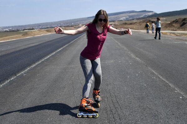 Una ragazza durante il corso sui pattini a rotelle nell'autostrada Tavrida in Crimea. - Sputnik Italia