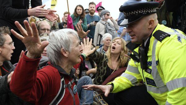 Сотрудник полиции общается с участницей акции протеста против загрязнения окружающей среды на улице в Лондоне - Sputnik Italia