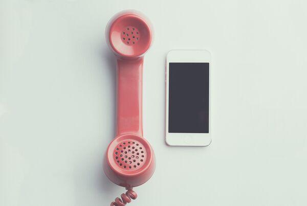 Vecchio telefono affianco a uno smartphone - Sputnik Italia