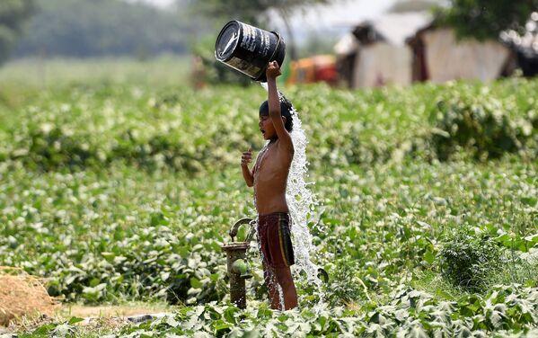 Un bambino versa l'acqua su se stesso per rinfrescarsi a New Delhi, India.  - Sputnik Italia
