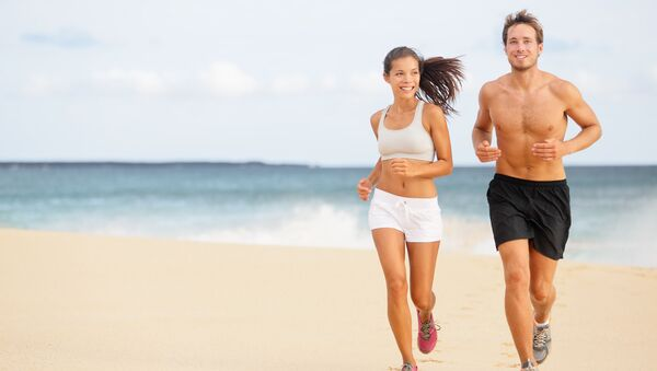 Una ragazza e un ragazzo corrono sulla spiaggia - Sputnik Italia