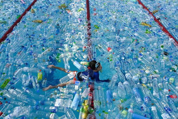 Bambino nuota nella piscina riempita con delle bottiglie di plastica durante la campania dedicata alla Giornata Mondiale degli Oceani a Bangkok, in Thailandia. - Sputnik Italia