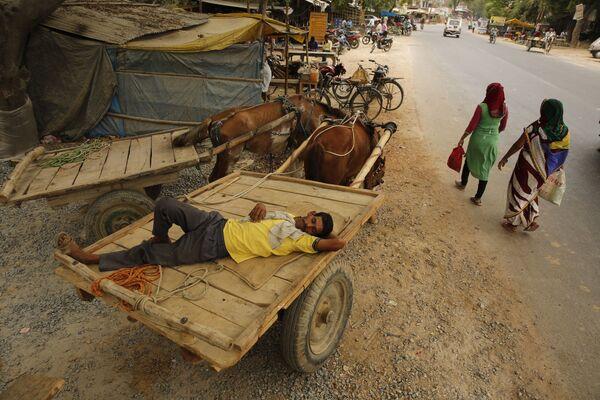 Uomo dorme in un carretto durante un'ondata di caldo anomalo in India. - Sputnik Italia