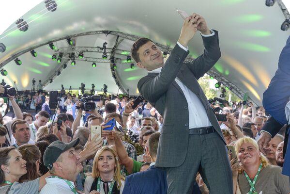Il presidente ucraino Vladimir Zelensky si fa un selfie al primo congresso del suo partito nel giardino botanico comunale a Kiev, Ucraina. - Sputnik Italia