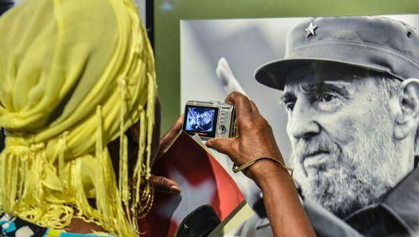Женщина фотографирует фото бывшего кубинского президента Фиделя Кастро - Sputnik Italia