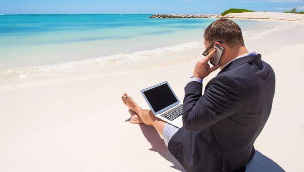 Uomo lavora al computer e telefono in spiaggia - Sputnik Italia