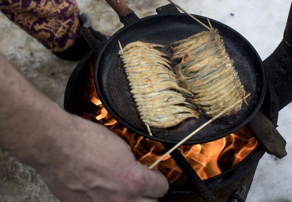 Un pescatore cucina degli sperlani appena pescati in un lago della Lituania - Sputnik Italia