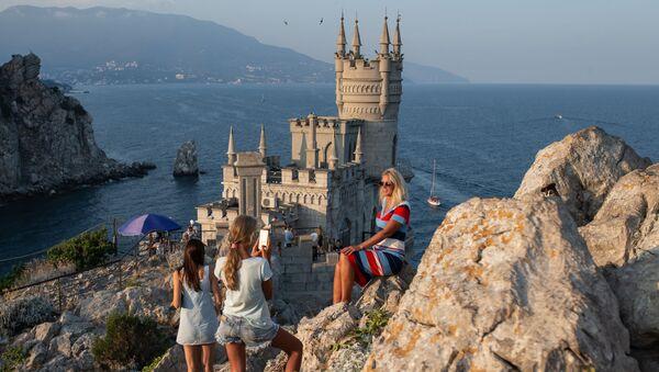 Отдыхающие фотографируются возле замка Ласточкино гнездо на береговой скале в поселке Гаспра в Крыму - Sputnik Italia