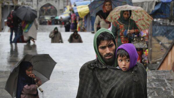 Un uomo di etnia Kashmir protegge suo figlio dal freddo a Srinagar, nel Kashmir controllato dall'India - Sputnik Italia