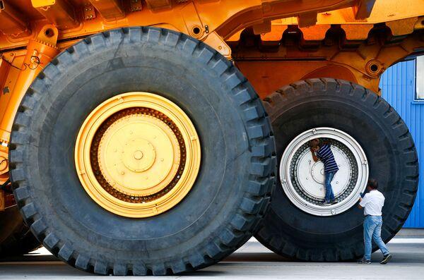 Una foto ricordo vicino alle ruote giganti di un'escavatrice BelAZ a Zhodino, in Bielorussia. - Sputnik Italia