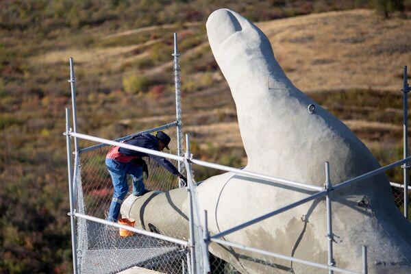 Un operaio impegnato in una delle parti più alte del monumento, la mano: la lunghezza del braccio è di 20 metri - Sputnik Italia