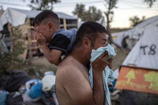 Uomo con in collo un bambino durante gli scontri vicino al campo di rifugiati Moria all'isola greca Lesbo. - Sputnik Italia