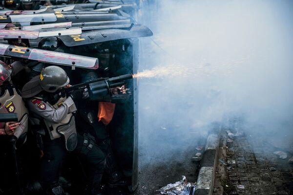 Un'agente di polizia usa gas lacrimogeno durante uno scontro con degli studenti manifestanti a Bandung, in Indonesia. - Sputnik Italia