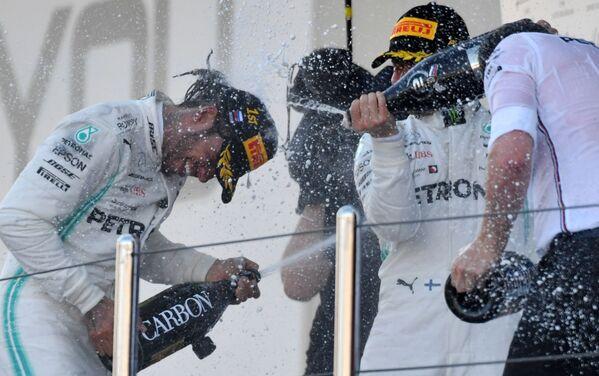 I piloti della Formula 1 Lewis Hammilton e Valtteri Bottas della squadra Mercedes festeggiano il loro successo al GP di Russia a Sochi. - Sputnik Italia