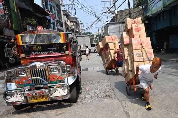 I lavoratori movimentano i carrelli carichi di merci lungo una strada nel quartiere Chinatown di Manila, il 22 ottobre 2019 - Sputnik Italia