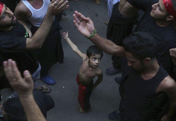 Bambino sciita con suo padre durante una processione in occasione della fine del periodo di lutto di 40 giorni per l'Imam Hussein, morto nel settimo secolo, in Lahore, Pakistan, il 20 ottobre 2019 - Sputnik Italia