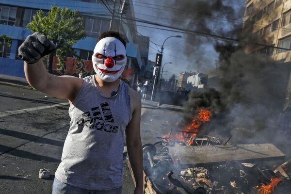 Un manifestante mascherato da clown durante le proteste a Santiago, Cile - Sputnik Italia