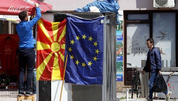 Un venditore affigge la bandiera macedone accanto a quella europea in una strada di Skopje - Sputnik Italia