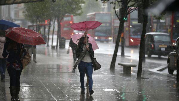 Donna con un ombrello durante una pioggia torrenziale a Londra - Sputnik Italia