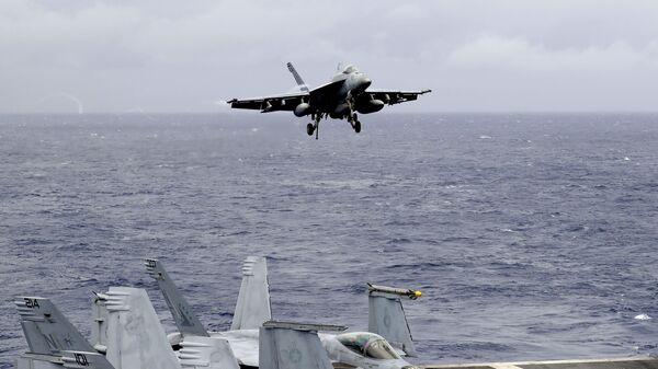 Un caccia americano in fase di atterraggio su una portaerei nel Mar cinese meridionale - Sputnik Italia