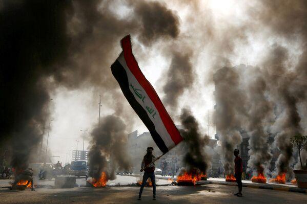 Un manifestante con la bandiera irachena durante le proteste a Najaf. - Sputnik Italia