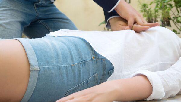 Мужчина делает женщине непрямой массаж сердца - Sputnik Italia