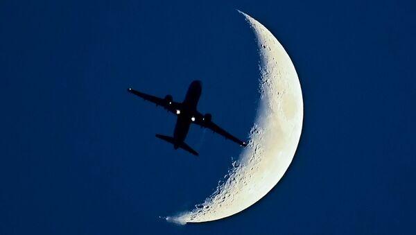 La sagoma di un aereo in volo con la Luna sullo sfondo - Sputnik Italia