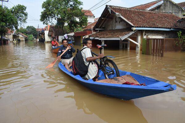 Abitanti si spostano in barca attraverso una strada allagata a Dayeuhkolot,  Indonesia, il 18 dicembre 2019 - Sputnik Italia