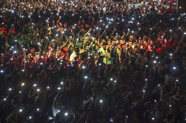 I cristiani si fanno luce con i telefonini durante una messa di Natale in Indonesia. - Sputnik Italia