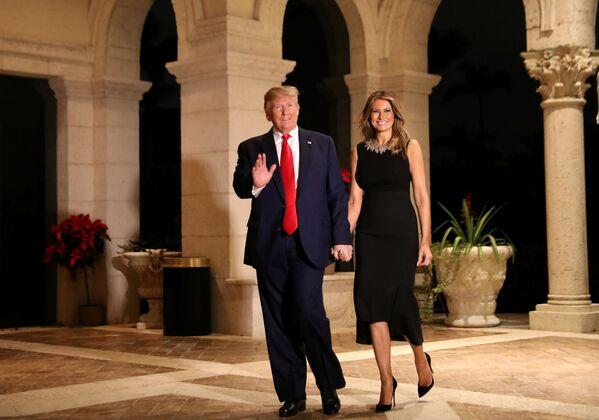 Il presidente statunitense Donald Trump e sua moglie Melania al party di Natale in Florida. - Sputnik Italia