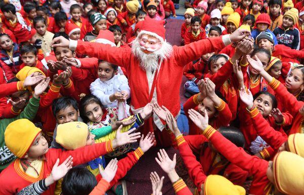 Una ragazza vestita da Babbo Natale distribuisce i regali ai bambini in India. - Sputnik Italia