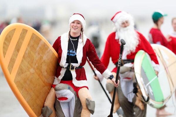 I partecipanti alla nuotata annuale dei surfer vestiti da Santa Claus negli USA. - Sputnik Italia