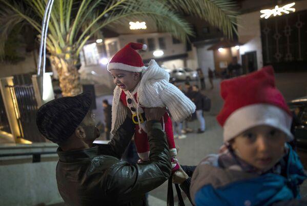 Un uomo gioca con il bambino prima della messa natalizia nella Striscia di Gaza. - Sputnik Italia