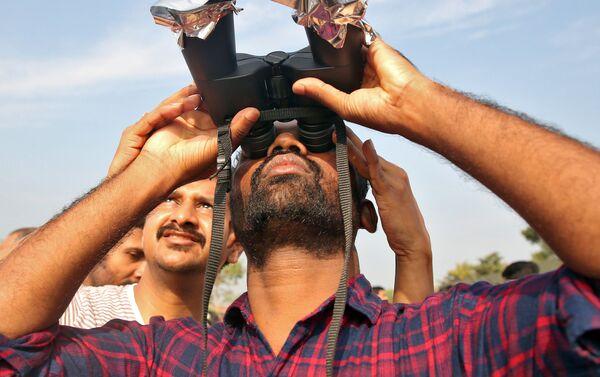 Un uomo osserva l'eclissi solare del 26 dicembre in India. - Sputnik Italia