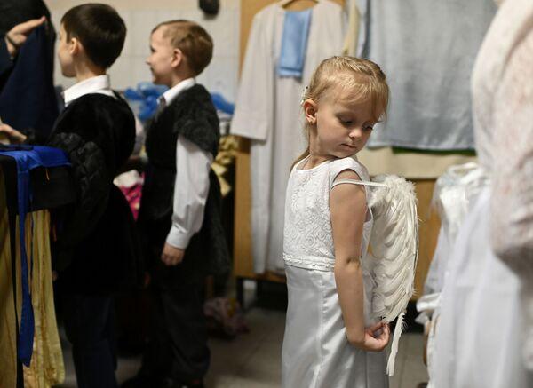 I bambini si preparano per l'esibizione in una chiesa cattolica a Omsk, Russia, il 24 dicembre 2019 - Sputnik Italia