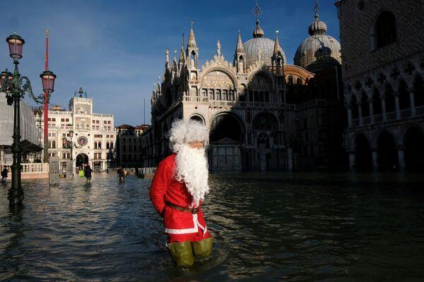 Un uomo vestito da Babbo Natale durante l'acqua alta a Venezia, Italia, il 23 dicembre 2019 - Sputnik Italia