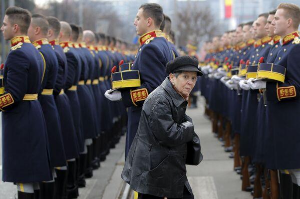 Una donna cammina tra i soldati di guardia d'onore durante un servizio commemorativo nel cimitero degli Eroi a Bucarest, Romania - Sputnik Italia