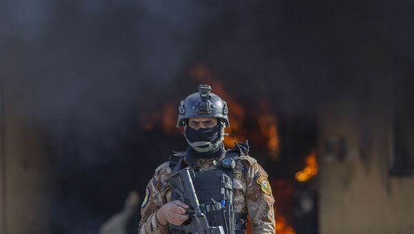 An Iraqi soldier stands guard in front of smoke rising from a fire set by pro-Iranian militiamen and their supporters in the U.S. embassy compound, Baghdad, Iraq, Wednesday, Jan. 1, 2020. - Sputnik Italia