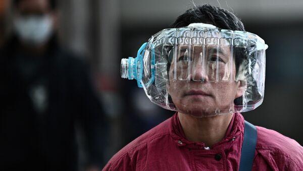 Un abitante di Hong Kong indossa una bottiglia come maschera per proteggersi dal coronavirus. - Sputnik Italia