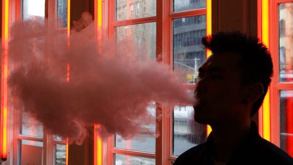 Un uomo esala vapore da una sigaretta elettronica - Sputnik Italia