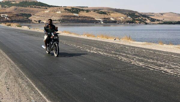 Мужчина с ребенком едут на мотоцикле неподалеку от моста Каракузат на северо-востоке провинции Алеппо - Sputnik Italia