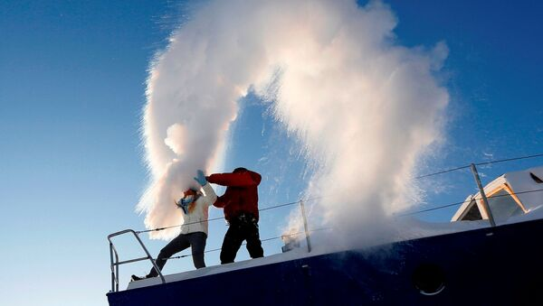 People throw hot water into the air, with the air temperature at about minus 34 degrees Celsius (minus 29.2 degrees Fahrenheit), outside Krasnoyarsk, Russia, January 22, 2018.  - Sputnik Italia