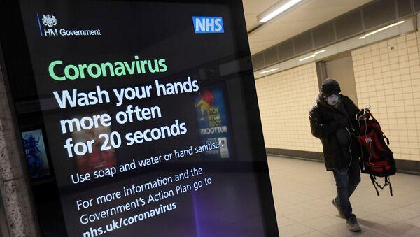 Un uomo con una maschera protettiva cammina davanti a una pubblicità della campagna sanitaria del governo britannico alla stazione della metropolitana di Victoria - Sputnik Italia