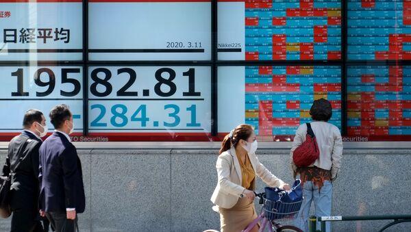 Persone con macherine a Tokyo allo sfondo di uno schermo con il codice Nikkei in calo - Sputnik Italia